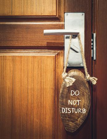 """quiet: """"do not disturb"""" sign hanging on the doorknob"""