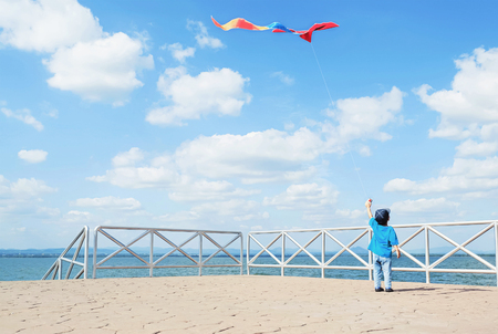 a little boy flying a kite on sea background photo