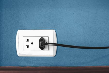 파란색 벽에 전기 플러그