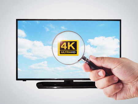 ultra modern: hand holding magnifying glass with 4k television display
