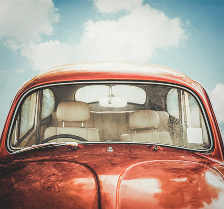 dirty car: old red car and sky background in retro filter