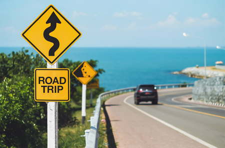 trips: road trip word and curvy road sign