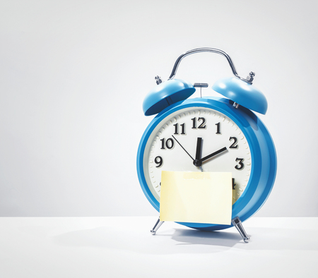 yellow notepad: yellow notepad and blue alarm clock Stock Photo