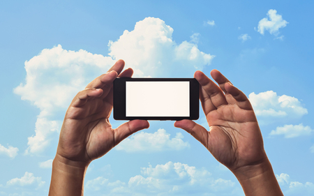 clouds making: smartphone in hand and blue sky background