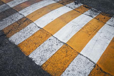 crosswalk: yellow and white crosswalk on the street