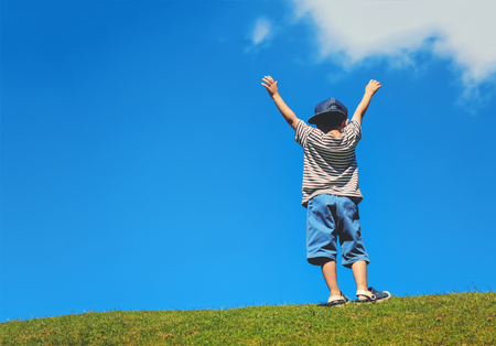 happy boy on green grass against blue sky background photo