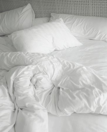 untidy: messy white bed sheets and pillow