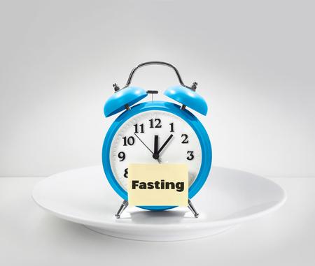 禁食的时候,闹钟放在白色的盘子上