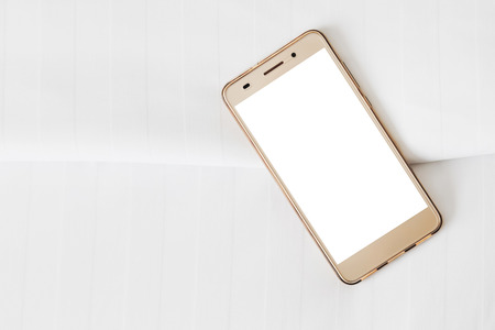 phone with white blank screen on white bed sheets Stock Photo