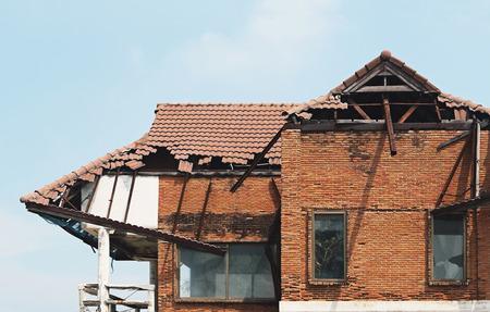 damaged roof: old broken house and sky background