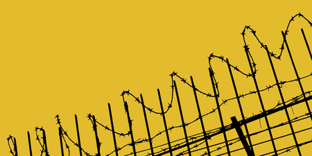 Tangled barbed wire fence on yellow background