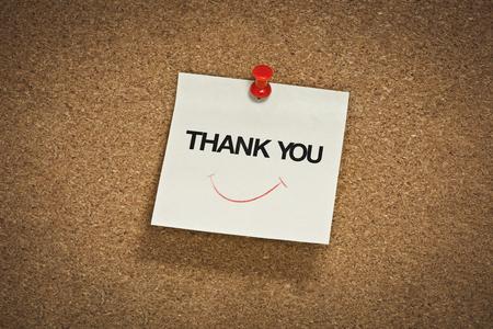 gracias palabra con símbolo de sonrisa en el bloc de notas Foto de archivo