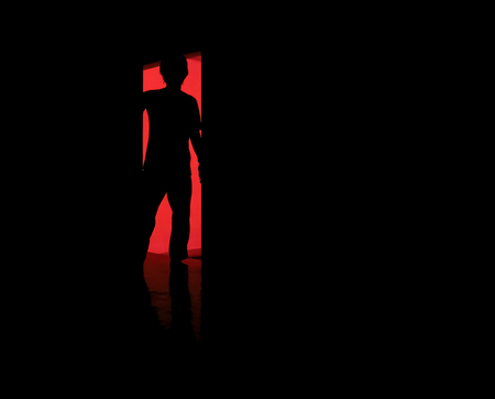 silhouette of a man standing in front of the door with darkness background Stock Photo