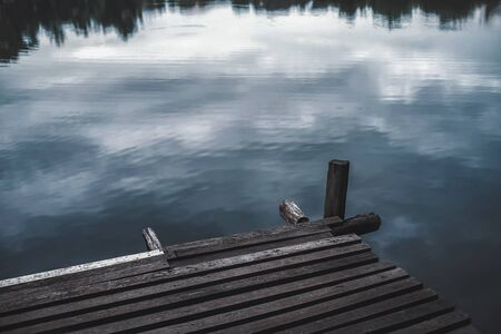 wooden jetty at lake on cloudy day