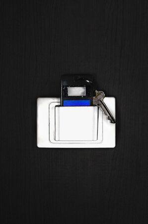 key card in electronic lock on gray wooden wall texture Archivio Fotografico