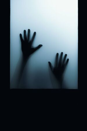 shadow of hand touch behind frosted glass door