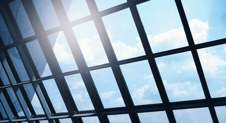 sunlight conveys business hopes. looking out into the sky outside the window of the office building. blue tone background