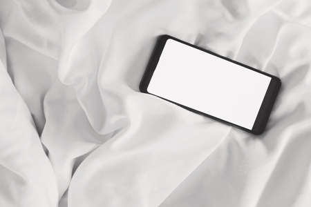 Blank screen mobile phone on the wrinkle white bed sheet.