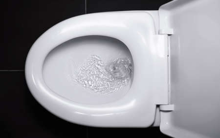 The white flush toilet bowl that the water is draining. concept of flushing away something. Stock fotó