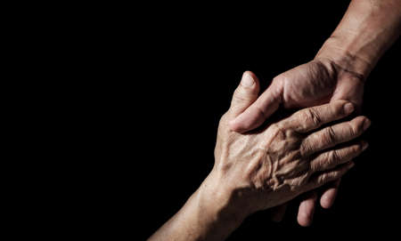 Senior health care provider. Home care for mature people. The caregiver makes elderly feel safe. Concept of family assistance and helping older adults. The aged wrinkled skin hand on black background. Stock Photo