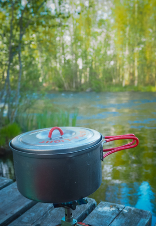 making dinner with littel gas stove at finnish river Banco de Imagens