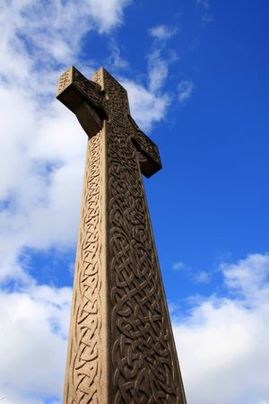A towering celtic cross photographed from below against a blue sky with white clouds enhancing its effect. photo