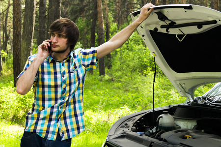 A sad man is waiting for help and calling the support service because his car broke down Stock Photo