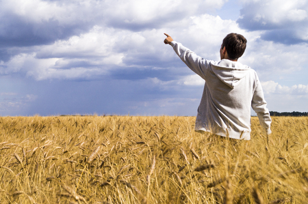 Man in a wheat field showing his fingers in the direction of the sky Stock Photo