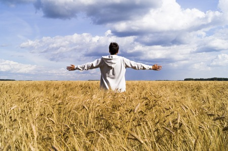 rushed: The man in the wheat field rushed his arms to the sides of freedom