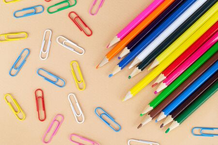 Lots of colorful pencils and paper clips on a nice beige background