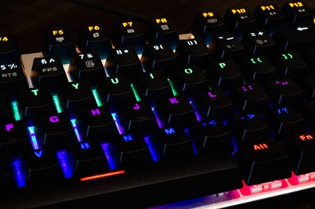Multi-colored professional gaming mechanical rgb keyboard on the table background Stock Photo