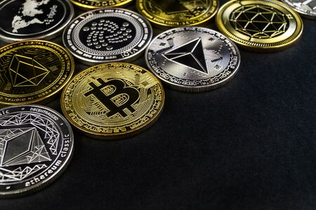 A lot of cryptocurrency coins lie on a dark surface background Фото со стока