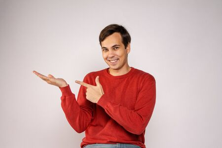 A young guy in a red sweater laughs. Portrait on gray background