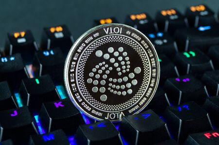 Coin cryptocurrency IOTA close-up of the colour-coded keyboard background