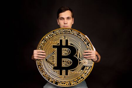 A young guy holds a symbol of the Bitcoin coin, a modern currency for exchange and purchases. Photo on a black background.