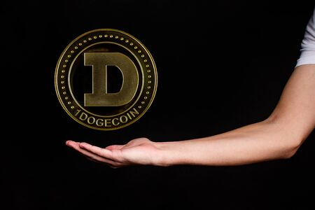 The symbol of the new popular cryptocurrency bitcoin with the image of hands on dark background