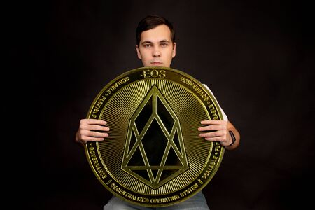 A young guy holds a symbol of the EOS coin, a modern currency for exchange and purchases. Photo on a black background.