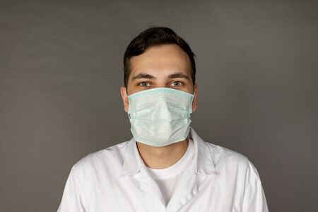Portrait of a doctor in a medical gown and protective mask. Photo on a grey background