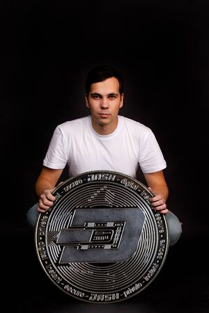 A young guy holds a symbol of the DASH coin, a modern currency for exchange and purchases. Photo on a black background 免版税图像