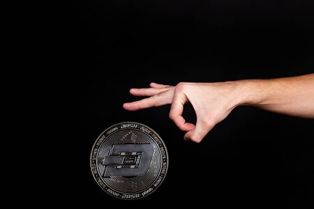 The symbol of the new popular cryptocurrency dash with the image of hands on dark background 免版税图像