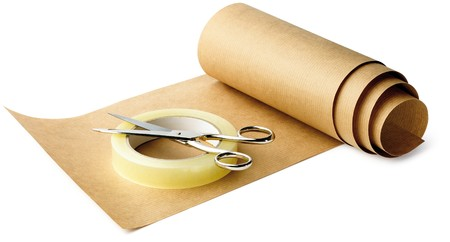brown paper and sticky tape and scissors ready for wrapping up on a white background