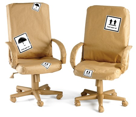 wrapped up: two office chairs all wrapped up in brown paper for a move Stock Photo