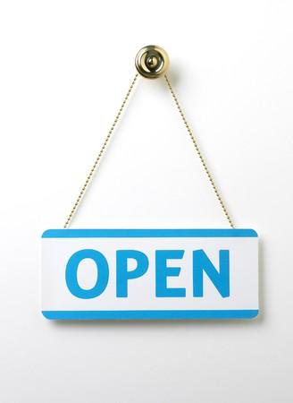 puerta abierta: un signo de azul de puertas abiertas de proceso en una cadena de lat�n sobre un fondo blanco