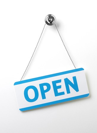 doors open: a process blue angled open door sign on a silver chain on a white background