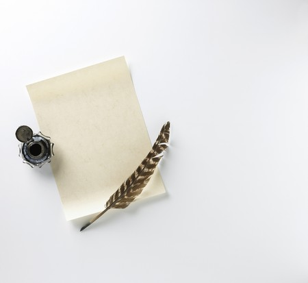 a blank letter, ink and feather quill on a white background