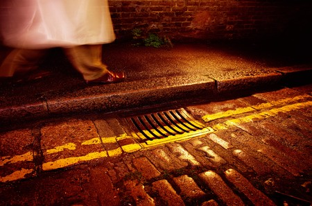 a man in a rain mac walking down a wet road with road lines past a drain Stock Photo