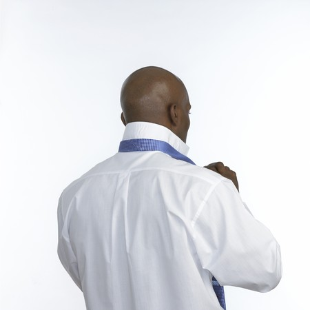 unrecognisable: an unrecognisable black man putting on a tie from behind on a white background Stock Photo