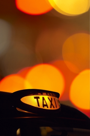 taxi sign: a british black taxi cab sign at night with colorful background 1 Stock Photo