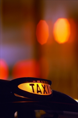 black cab: a british london black taxi cab sign at night with colorful background 2