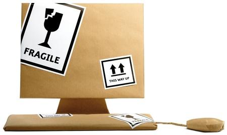 ordinateur, clavier et souris enveloppés dans du papier brun isolé sur fond blanc, prêts à déménager